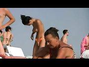 Oben ohne Frau mit großen Titten am Strand